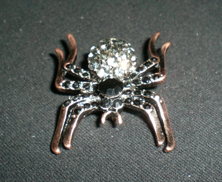Kleine bronzefarbene Spinne mit schwarzem und weißem Strass